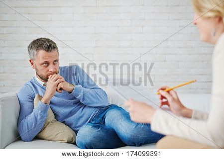 Worried bearded patient sitting on sofa with legs and listening to his female psychiatrist with concentration