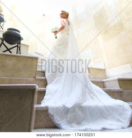 Skirt And Veil Lie On The Footsteps While Bride Goes Upstairs