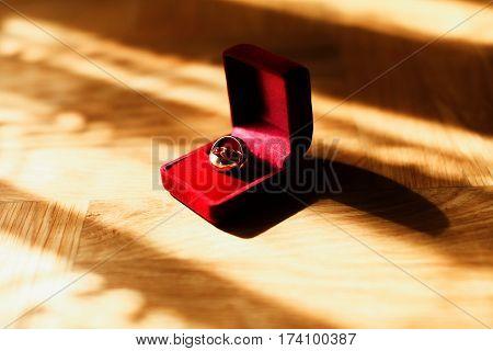 Wedding Rings In Red Velvet Box Lie On The Floor In The Rays Of Sunshine