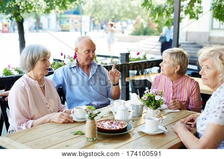 Three pretty senior women sitting at cafe table with coffee and cheesecake while their male friend entertaining them with small talk