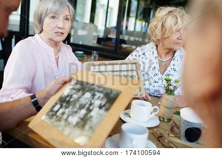 Elderly woman looking into distance thoughtfully while telling her friends story of her childhood and showing them black-and-white photos in outdoor cafe