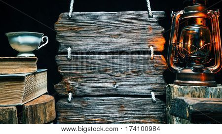 Porcelain cup of tea on old books with kerosene lamp and triple wooden signboard. Isolated over black