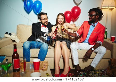 Two middle-aged men and one young woman sitting in living room decorated for New Year celebration and toasting with alcohol