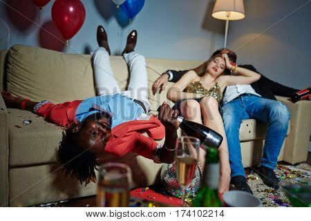 Group of glamorous friends relaxing on sofa after wild house party, they holding champagne and beer bottles in hands while having nap