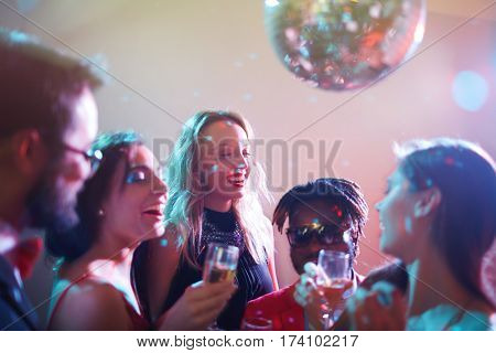 Dressy multiethnic group of friends gathered together and celebrating momentous event in nightclub, they laughing and drinking alcohol