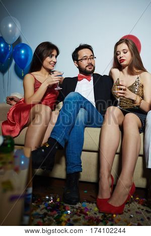 Elegant-looking friends hanging out at home with champagne and alcohol cocktails, they chatting animatedly and enjoying each others company