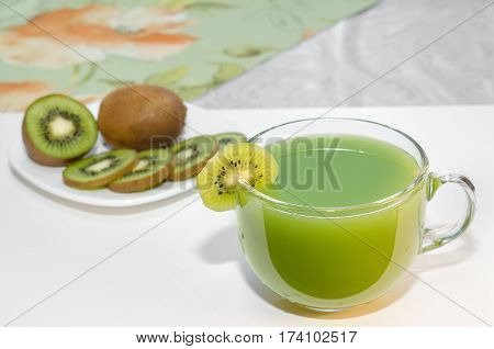 Fresh kiwi juice in a Cup and fruits on the plate. Selective focus, space for text.