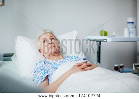 Lonely senior woman lying thoughtful on white sheets in hospital ward