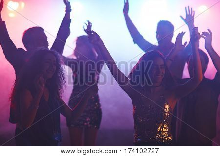 Group of young dressy girls and guys dancing in night club with their hands up
