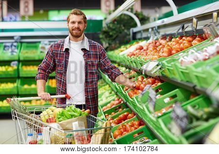 Portrait of young bearded man in checked shirt stretching arm towards tomato while looking at camera with toothy smile in supermarket