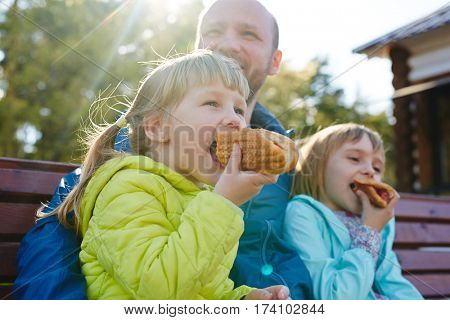 Waist-up portrait of cute little girl with two ponytails sitting in park with her elder sister and middle-aged dad and eating delicious hotdog, lens flare