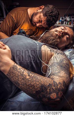 Man wearing gloves making a tattoo in tatoo salon./Professional tattooer makes cool tattoo in tattoo studio.