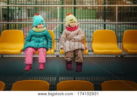 Two girls sit on the grandstand and watch football match