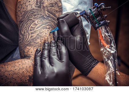 Tattoo master posing in tatoo salon./Man wearing gloves makes tattoo in tattoo studio.