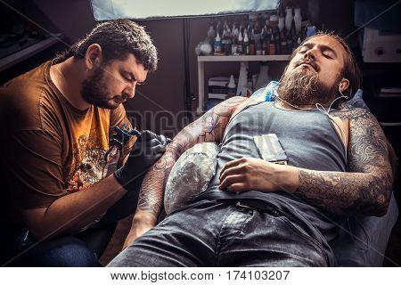 Tattoo artist makes tattoo in tattoo parlour.