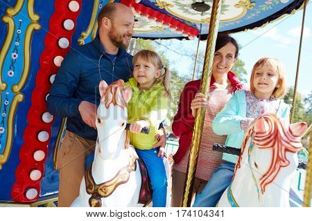 Portrait of pretty middle-aged couple in windbreakers standing on colorful carousel while their cute little daughters riding on it