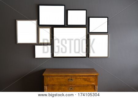 Blank frames in different sizes on a gray wall with a wood dresser in the front
