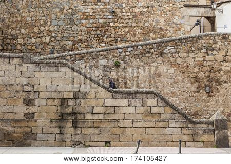 Plasencia Spain - February 15 2017: Man Ascending stone steps at Plasencia old town Caceres Extremadura Spain