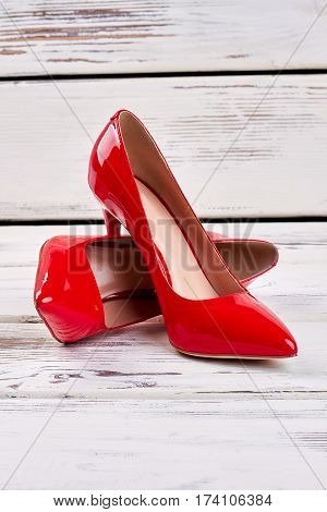 Red shoes on wood. Stylish women's footwear.