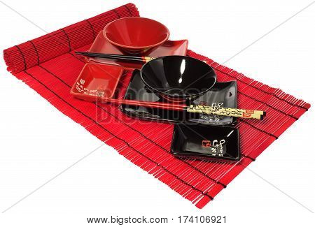 Red And Black Set Of Dishes For Sushi On The Red Wooden Mat.