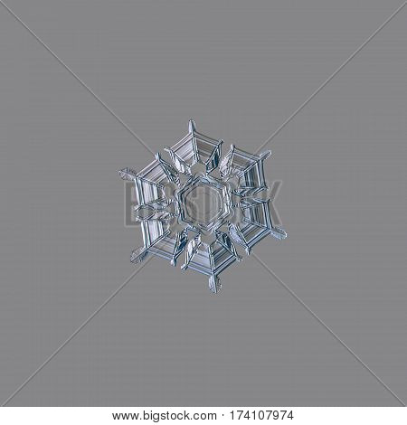 Macro photo of real snowflake: medium size snow crystal of stellar plate type with glossy, relief surface, simple shape and inner pattern with hexagonal symmetry, containing straight lines.