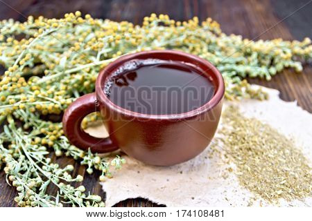 Tea With Wormwood In Brown Cup On Board