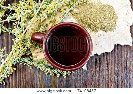 Tea With Wormwood In Clay Cup On Board Top