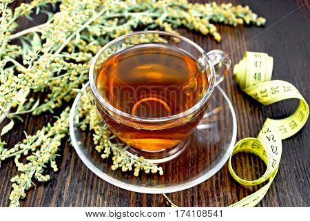 Tea With Wormwood In Glass Cup And Meter On Board