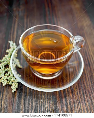 Tea With Wormwood In Glass Cup On Board