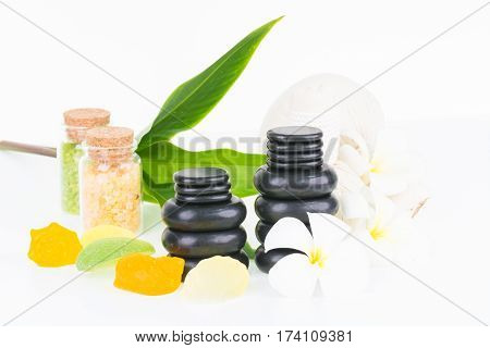 Tropical spa getaway with hot stones, herbal compress ball, seashell shaped soaps and flowers on white background