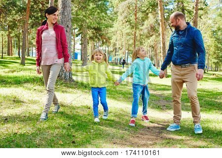 Lovely family of four in bright windbreakers holding hands and having walk in spring park with pine forests