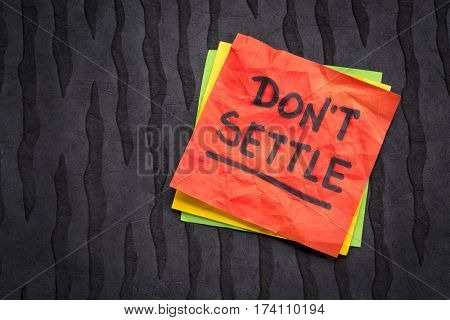 Do not settle - motivational advice or reminder on a sticky note against black lokta paper