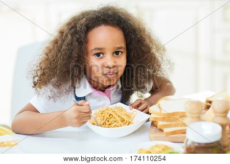 Curly little girl with full mouth looking at camera while chewing tasty pasta, bread slices, chocolate spread bottle, salt and pepper shakers located on table