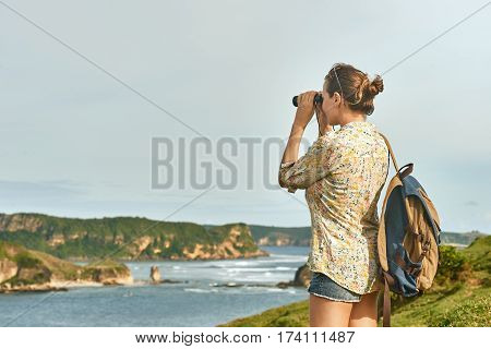 Happy young woman tourist with backpack enjoying sunny coast view on sunrise. Traveling along mountains and coast freedom and active lifestyle concept.