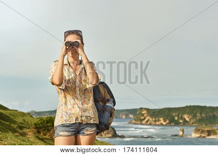 Happy young woman tourist with backpack enjoying sunny coast view. Traveling along mountains and coast freedom and active lifestyle concept.