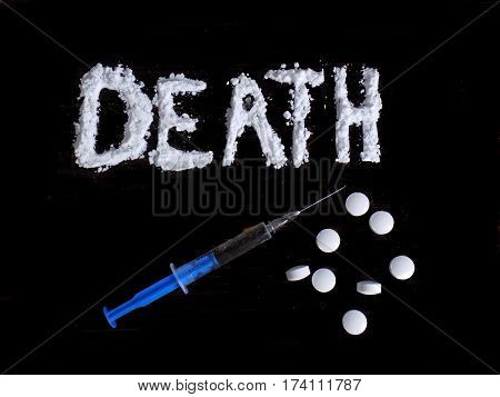 Cocaine drug powder in death word shaped, injection syringe and pills on black background