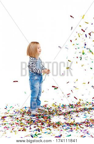 Cute little blond girl with burst of sparkling confetti against white background, tossing it up and watching it fall down smiling