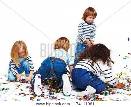 Four little children crawling on floor busy picking up bright foil confetti and playing with it, ready to toss it up