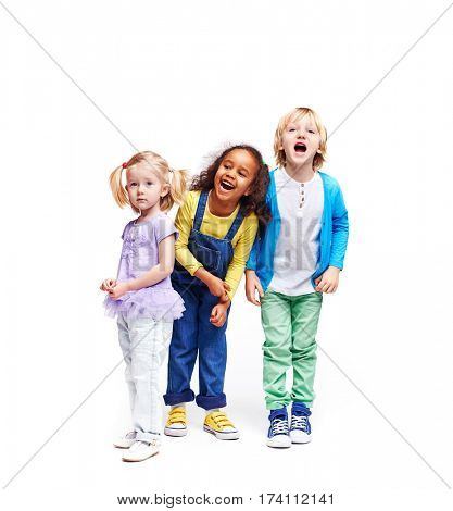 Studio portrait of children against white background:  full body shot of three kids in colorful clothes, African girl, blond boy and cute little girl, laughing and screaming loudly with mouths open