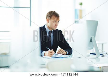Portrait of successful young business analyst busy working alone in modern office, checking statistics report with graphs while sitting at computer desk