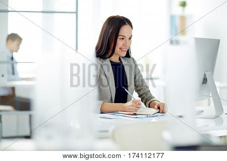 Portrait of successful Asian businesswoman busy working at desk in modern office, making notes in planner and looking at computer screen