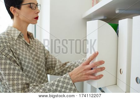 Side view of confident contemporary businesswoman wearing creative short haircut and red lipstick taking a white folder from documentation case in office