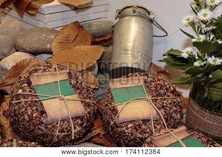 Italian Sheep's Milk Cheese: Aged Pecorino, Dry Leaves And Antique Metallic Milk Container
