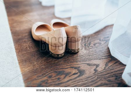 Peach glossy women's wedding shoes on brown wooden floor and tulle. Close-up, backside view