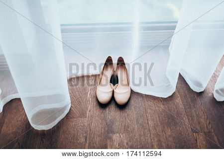 Peach glossy women's wedding shoes on brown wooden floor and tulle. Close-up, top view
