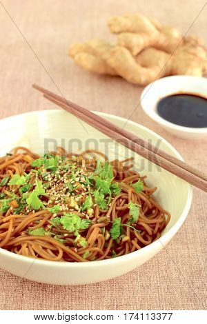 Soba noodle with ginger garlic soy sauce garnish with sesame seeds and parsley