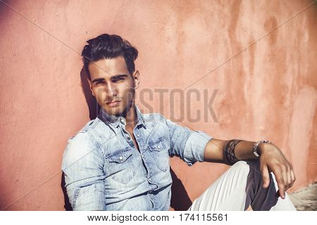 Portrait of handsome man with tattoo on arms sitting on cement stairs while leaning on wall, looking away to a side
