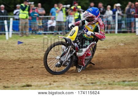 SWINGFIELD, UK - AUGUST 18: A member of the Australian grasstrack team rides into the top corner of the circuit at speed during the Longtrack World Championships on August 18, 2013 in Swingfield