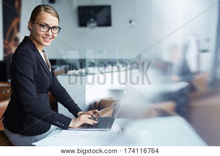 Young successful businesswoman smiling cheerfully looking to camera while working with laptop and documents in restaurant lounge during coffee break
