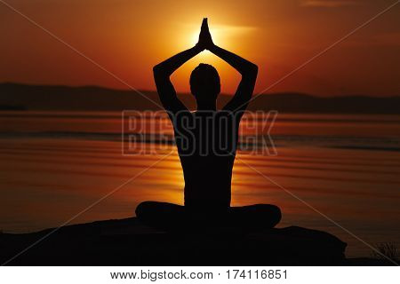 Silhouette of man sitting in lotus pose, holding his arms above head in namaste and meeting sunset